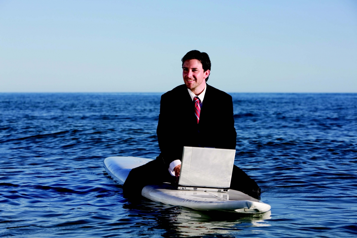 Man with laptop on surfboard business risks employee leave